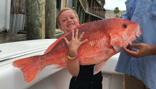 Young boy holds giant red snapper fish he caught on a Galveston deep sea fishing charter
