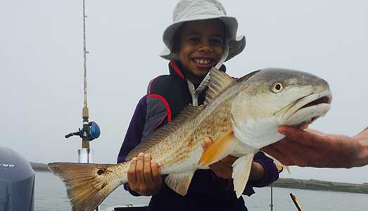 Young kid holding redfish caught on a Galveston fishing trip