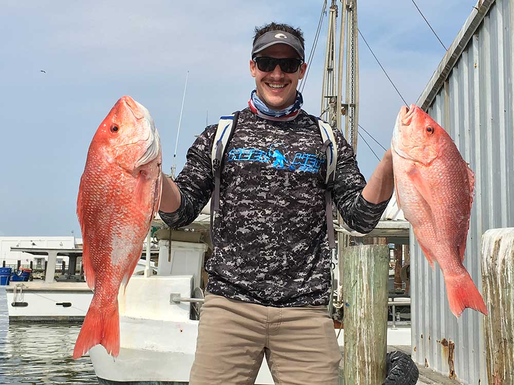 Angler holds up his Galveston Red Snapper catch from a Red Snapper fishing trip
