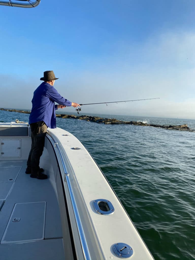 Man casts fishing rod over side of boat