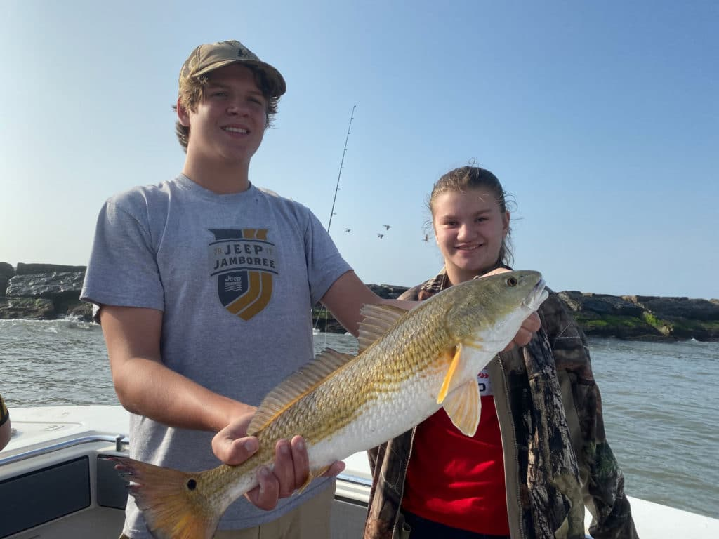 Two teenagers holding redfish caught in Galveston in February