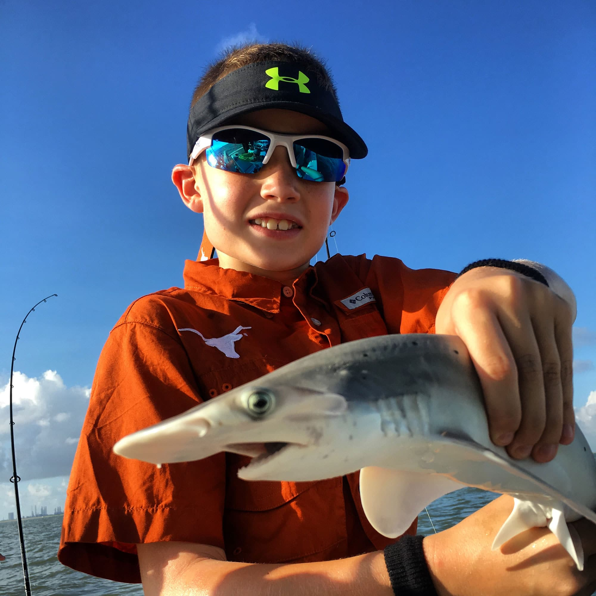 Young boy holding small shark