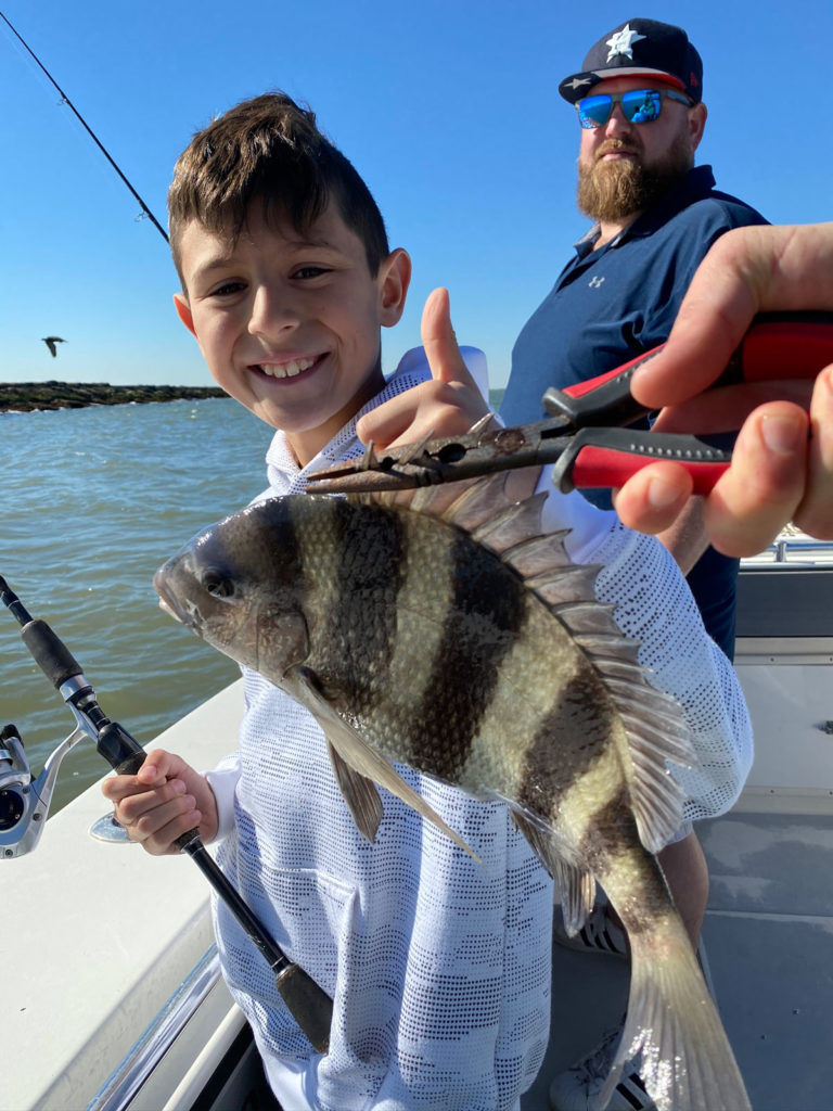 Young boy holds sheepshead fish caught in February