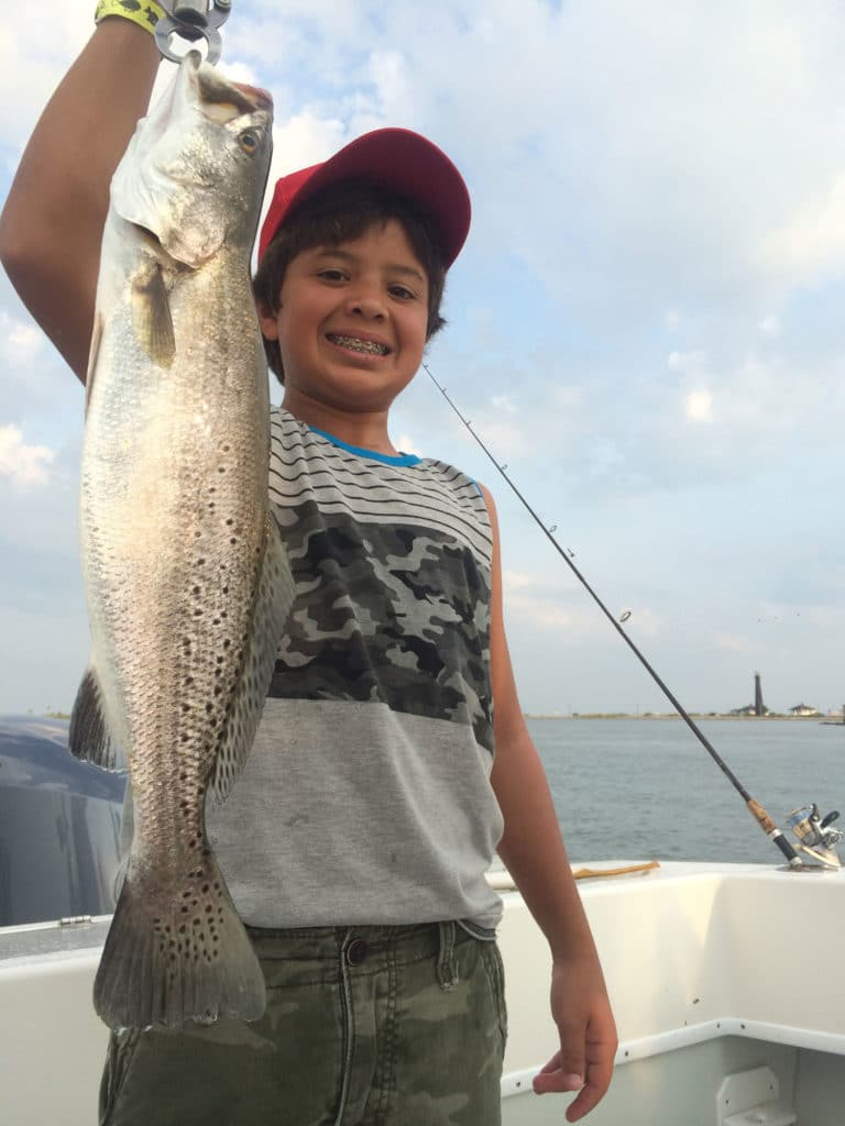 Young boy with braces holding speckled trout