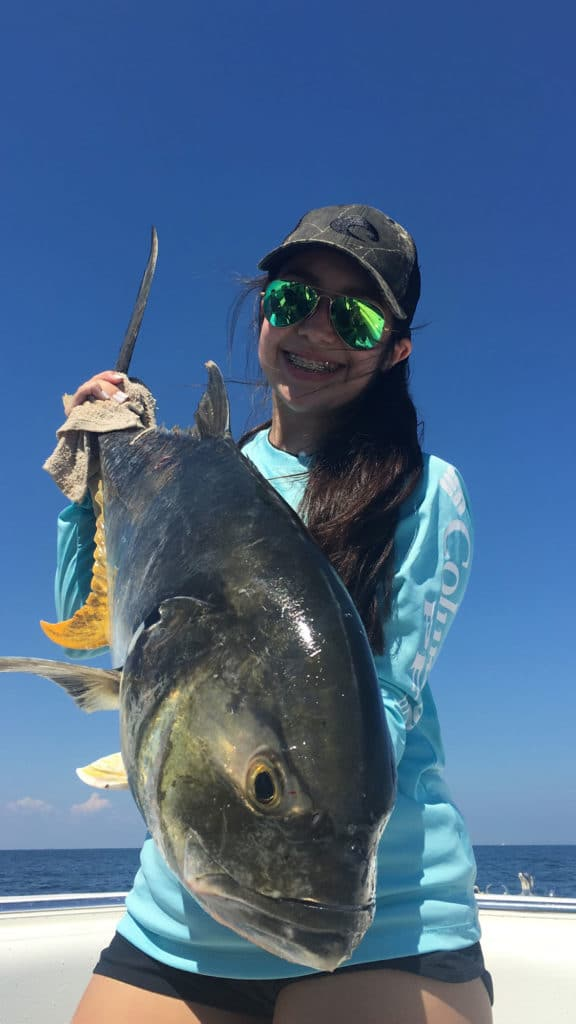 Young girl holds up a yellowfin tuna on a boat in beautiful Galveston Spring weather