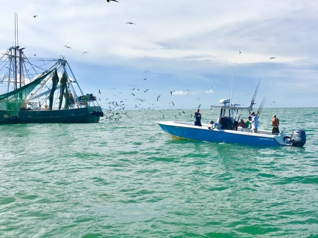 Galveston fishin charter boat alongside a shrimping boat