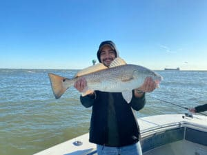 Man in hood smiling and holding fresh caught redfish