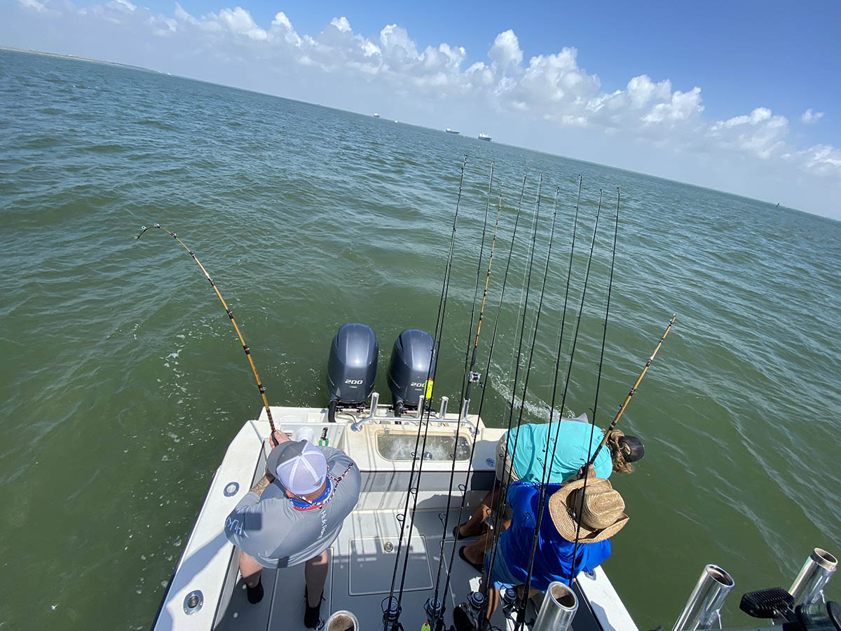 Overhead image of 3 anglers working to reel in a fish
